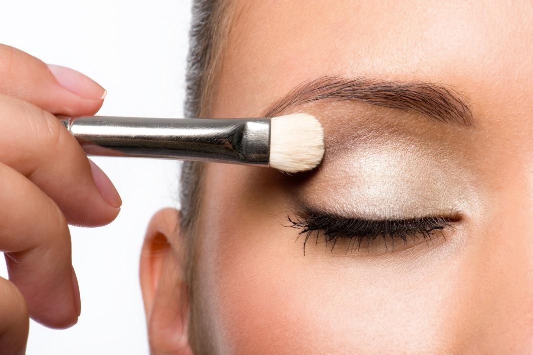 woman applying eyeshadow on eyelid
