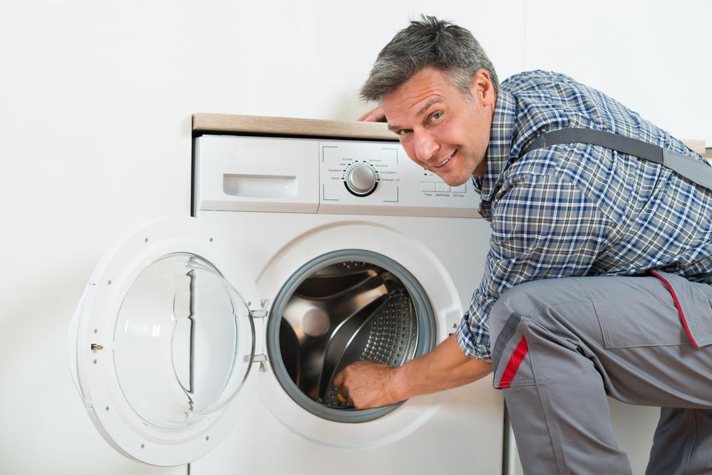 Repairman Checking Washing Machine At Home